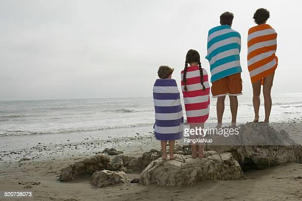 Vue arrière du couple avec deux enfants recouvert de serviettes