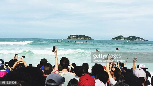Rear View Of Crowd Photographing Sea Against Sky