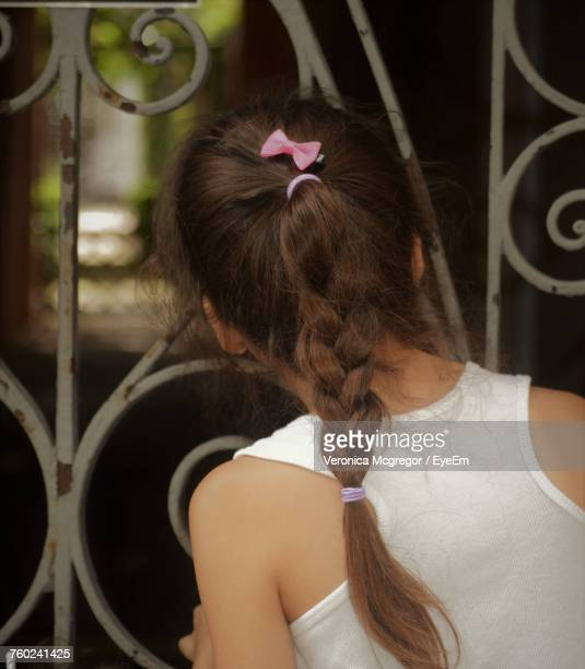 Rear View Of Curious Girl Looking Through Metal Fence