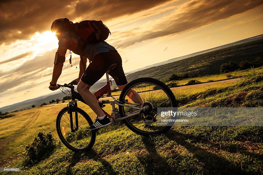 Rear view of cyclist climbing the mountain