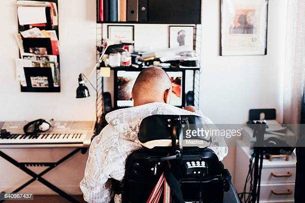 Rear view of disabled musician sitting on wheelchair in recording studio