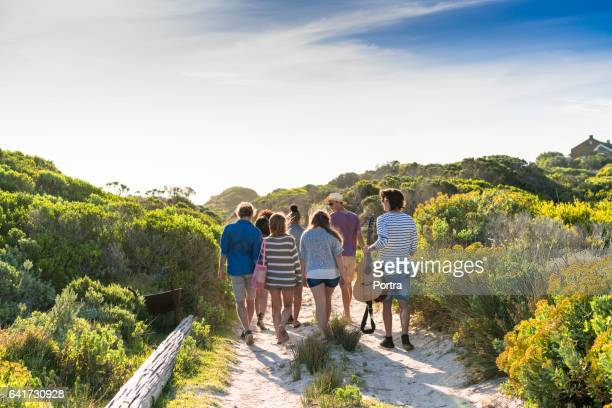 Rear view of diverse friends walking on dirt road