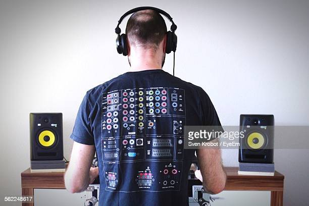 Rear View Of Dj Playing Music At Home
