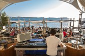 Rear view of DJ selecting music, Cafe Del Mar, Ibiza, Spain