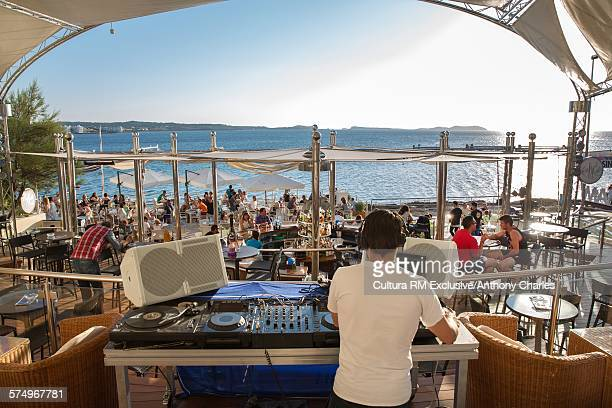 Rear view of DJ selecting music, Cafe Del Mar, Ibiza, Spain