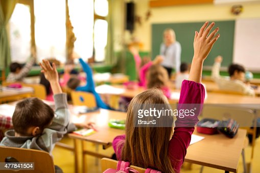 Rear view of elementary school children with raised arms.