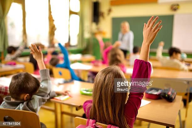Vista posteriore di scuola elementare di bambini con le braccia sollevata.