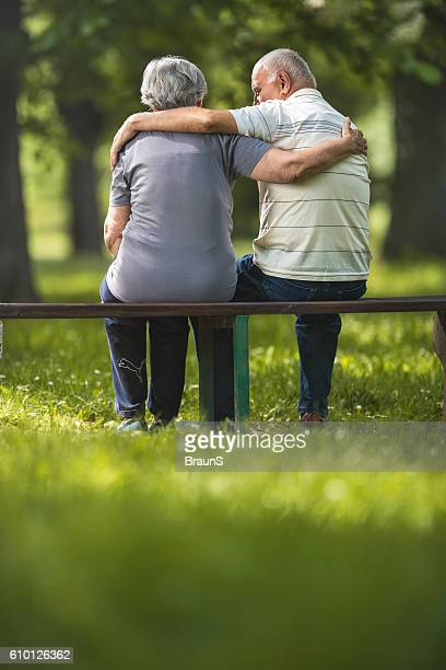 Rear view of embraced senior couple relaxing on a bench.