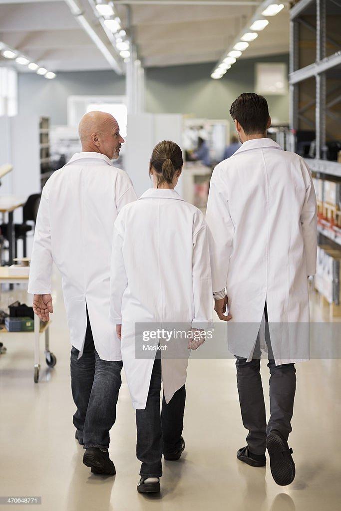 Rear view of engineers walking in factory