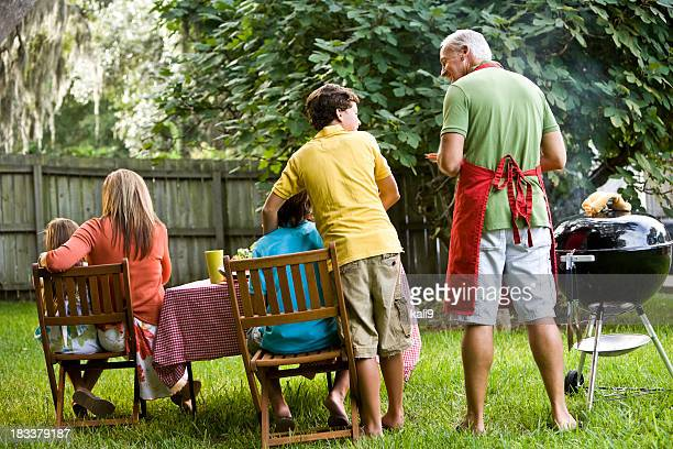 Rear view of family backyard barbeque
