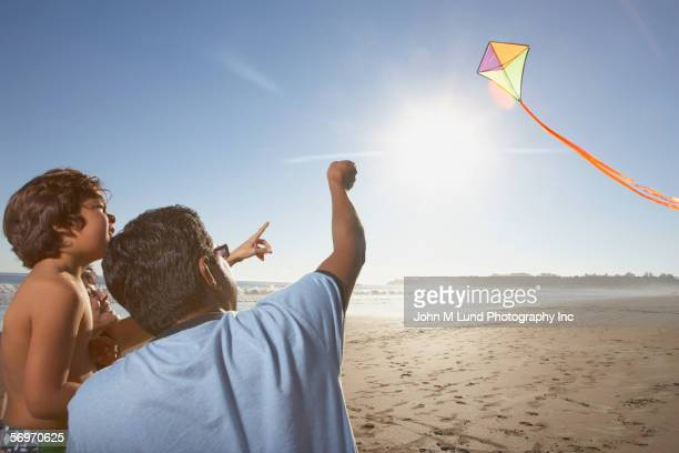 Rear view of family flying kite at beach