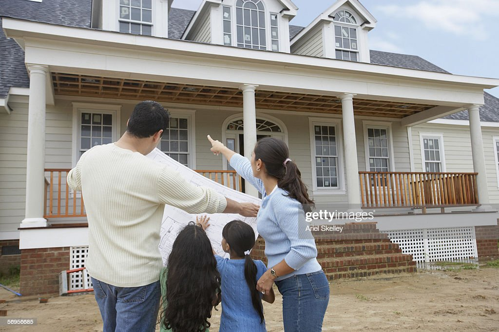 Rear View Of Family Looking At House Plans And Pointing To House