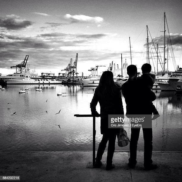 Rear View Of Family Standing In Front Of Yachts Moored On Sea