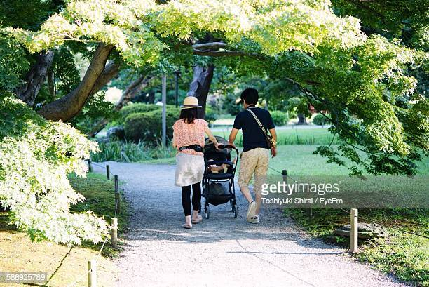 Rear View Of Family With Baby Carriage Walking On Footpath In Park