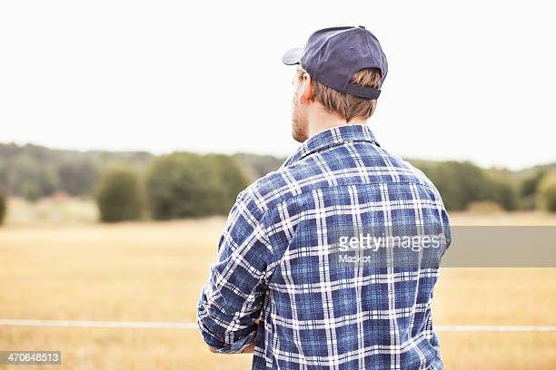 Rear view of farmer standing at field