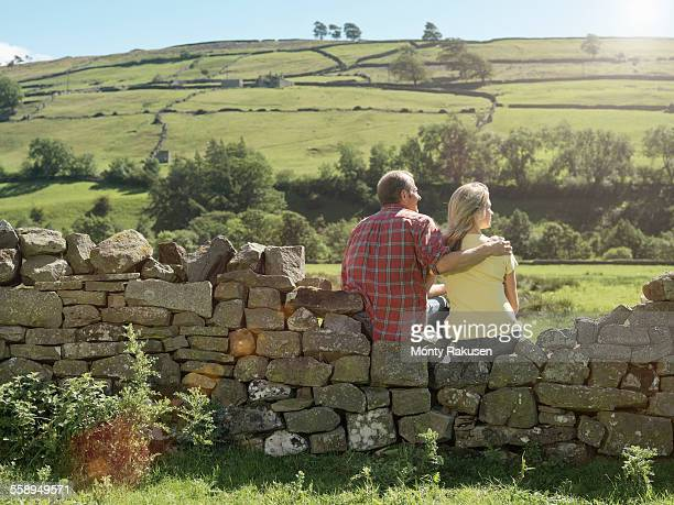 Rear view of farming couple looking out from dry stone wall over field