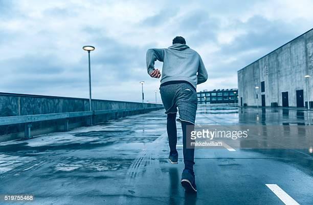 Rear view of fast runner running on street