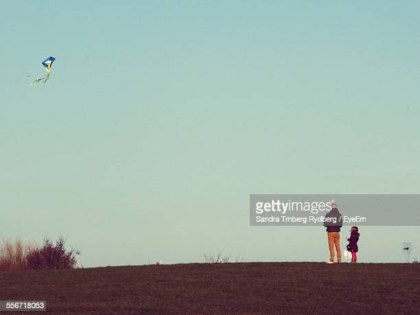 Rear View Of Father And Daughter Flying Kite In Clear Sky