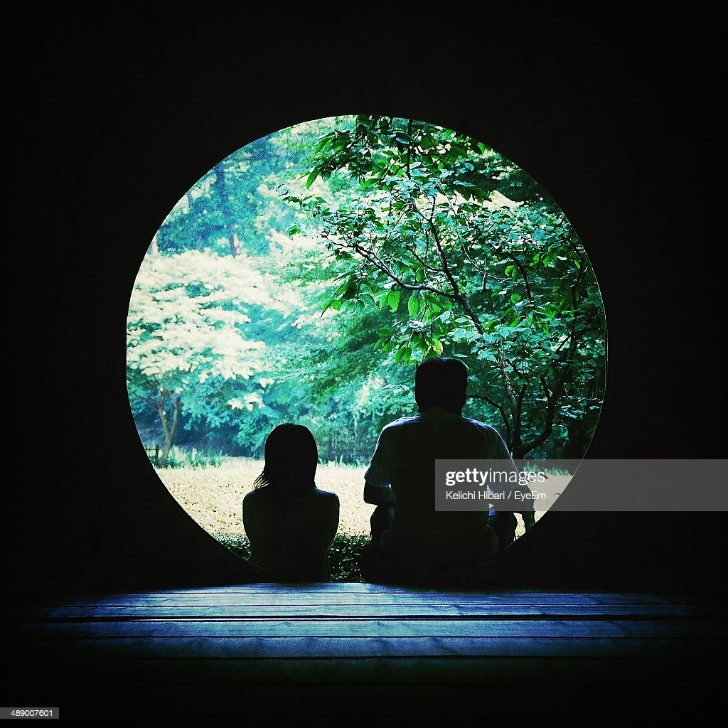 Rear view of father and daughter looking at trees while sitting on steps at circular doorway : Stock Photo