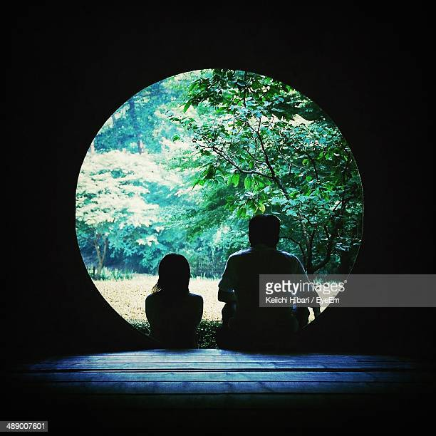 Rear view of father and daughter looking at trees while sitting on steps at circular doorway