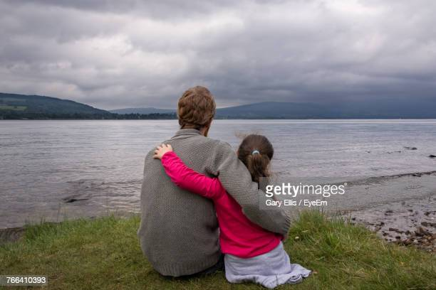 Rear View Of Father And Daughter Sitting By Sea Against Cloudy Sky