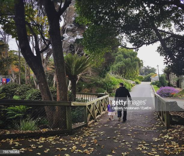 Rear View Of Father And Daughter Walking On Footpath
