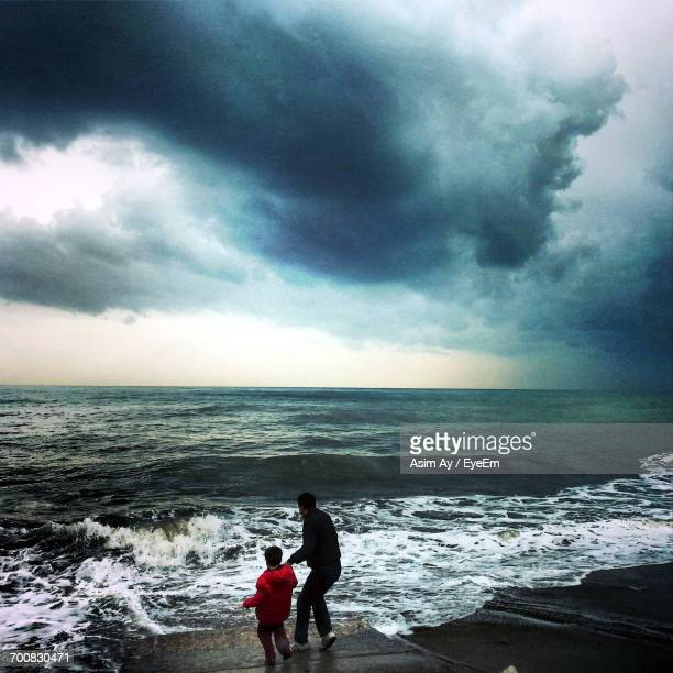 Rear View Of Father And Son Entering In Sea Against Cloudy Sky