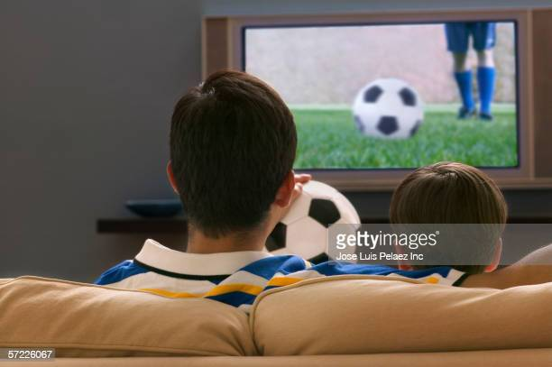 Rear view of father and son on couch watching soccer on television