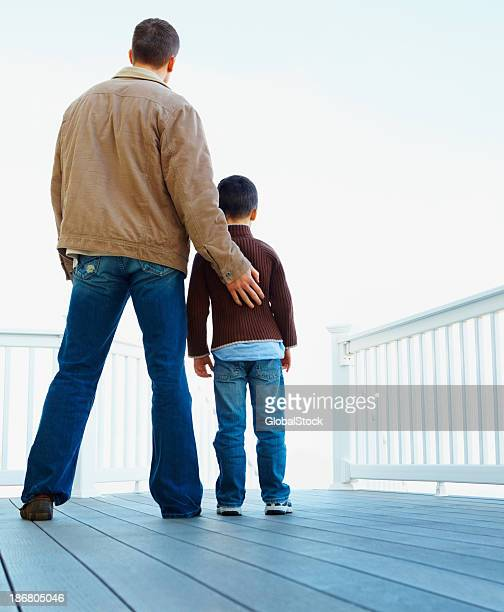 Rear view of father and son standing together at porch