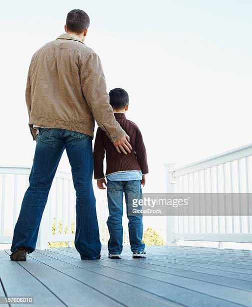 Rear view of father and son standing together on porch