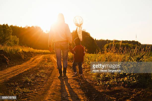 Rear view of father and son with butterfly net walking along dirt track at sunset, Sarsy village, Sverdlovsk Region, Russia