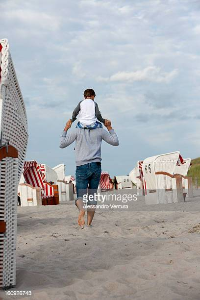 rear view of father carrying young son on his shoulders