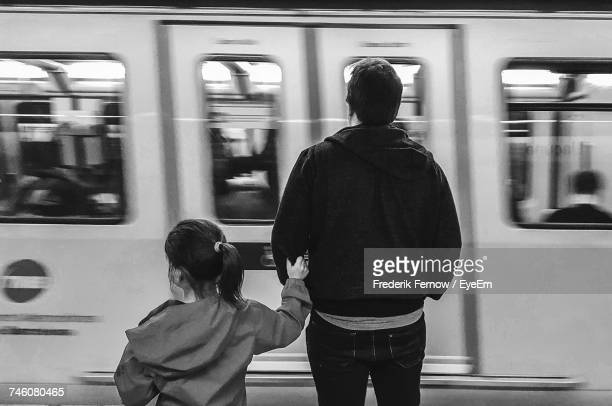 Rear View Of Father With Daughter Standing By Train At Subway Station