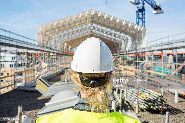Rear view of female construction worker at site