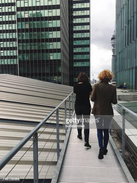 Rear View Of Female Friends Walking On Footbridge In City