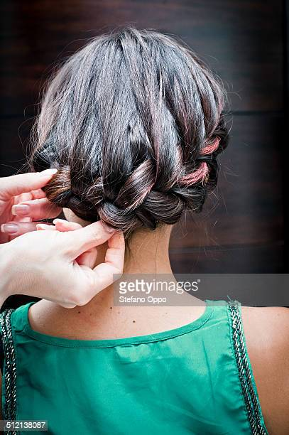 Rear view of female hairdresser braiding young woman's hair in hair salon