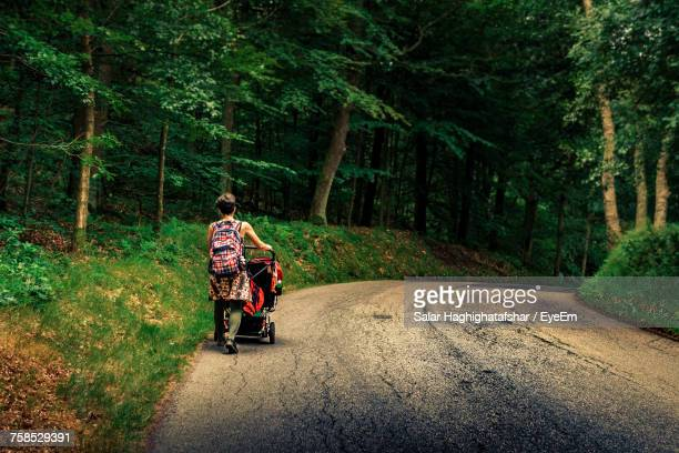 Rear View Of Female Hiker With Backpacks Walking On Road In Forest