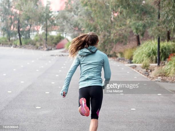 Rear view of female runner running by park