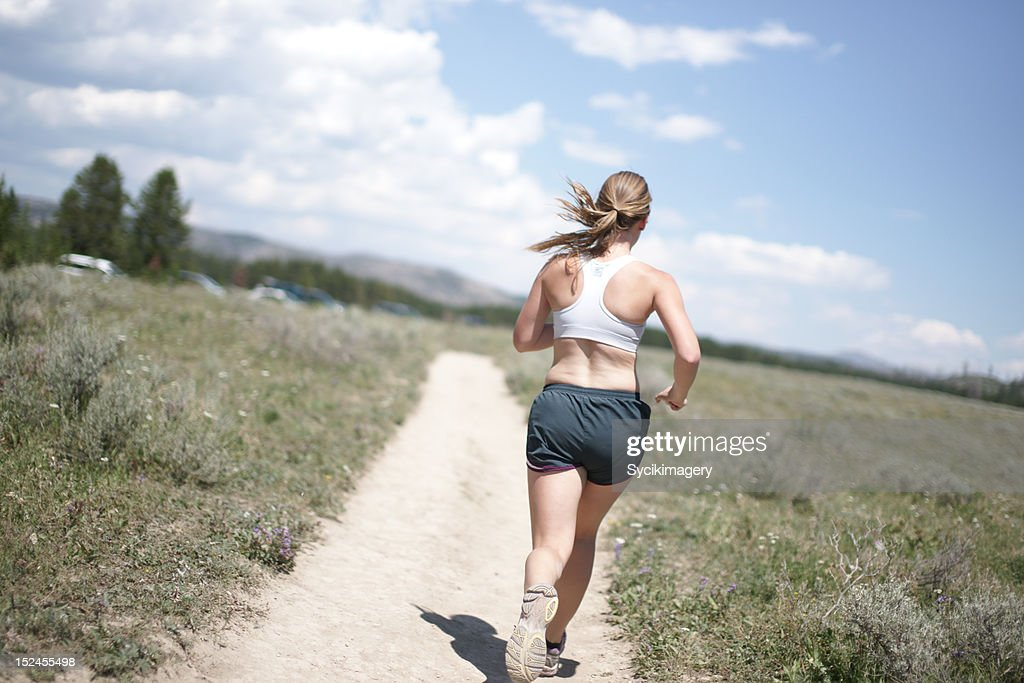Rear view of female running : Stock Photo