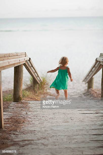 Rear view of female toddler toddling down to beach, Anna Maria Island, Florida, USA