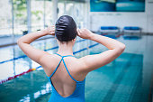 Rear view of fit woman putting on swim cap at the pool