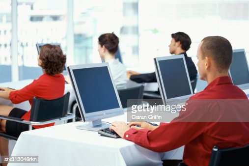 rear view of four business executives using computers in an office : Stock-Foto