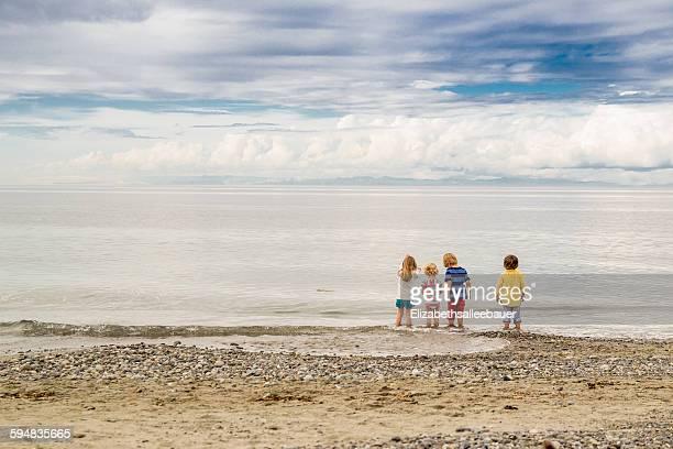 Rear view of four children standing on the beach