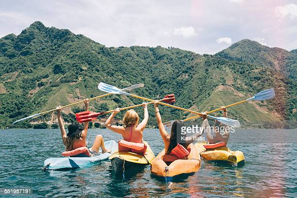 Rear view of four female friends celebrating in kayaks on Lake Atitlan, Guatemala