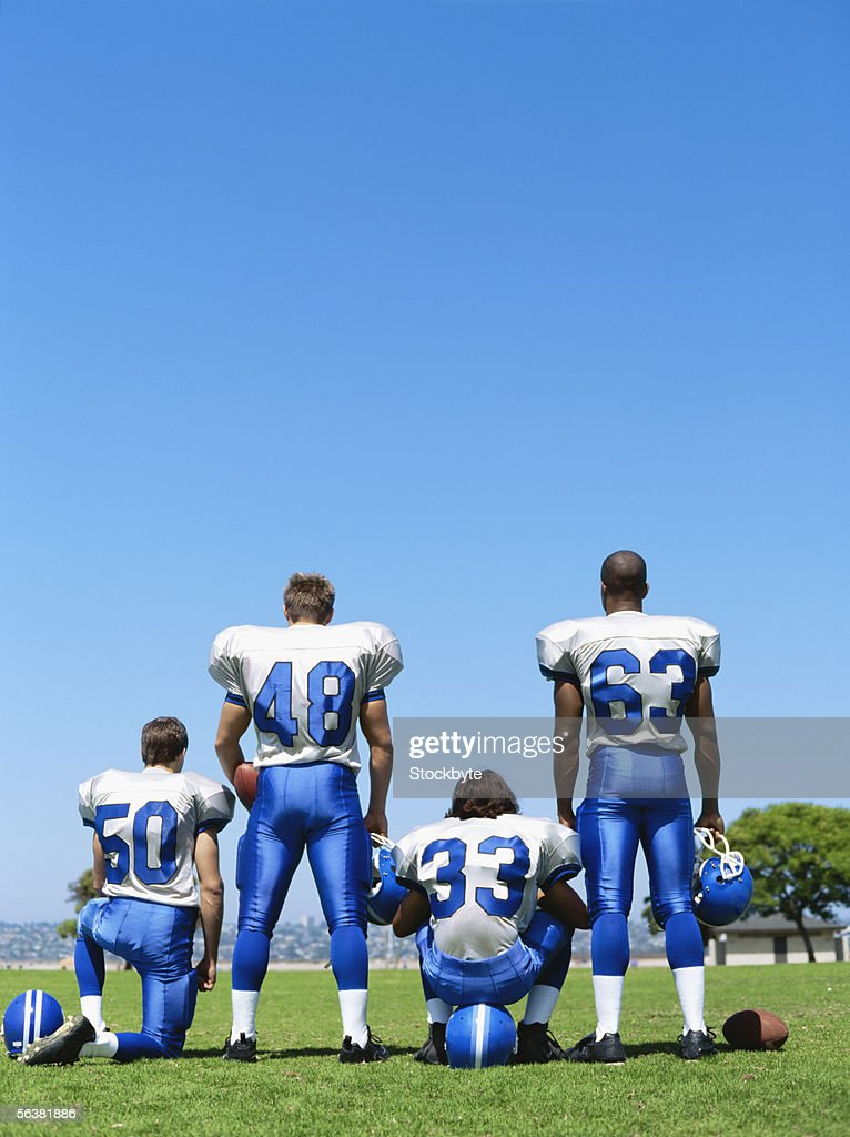 rear view of four football players on a football field