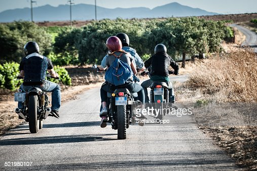 Rear view of four friends motorcycling on rural road, Cagliari, Sardinia, Italy