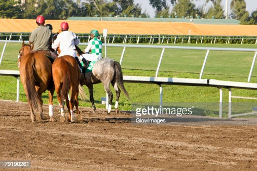 Rear view of four jockeys riding horses on a horseracing track : Stock Photo
