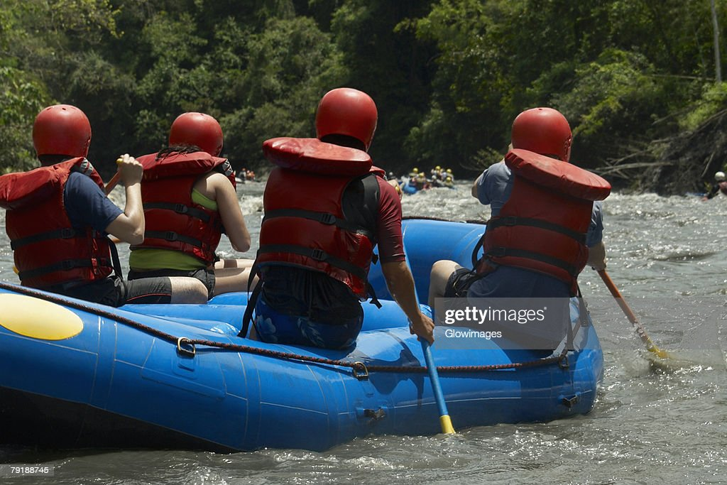 Rear view of four people rafting in a river : Stock Photo