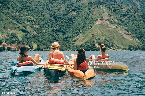 Rear view of four young female friends kayaking on Lake Atitlan, Guatemala