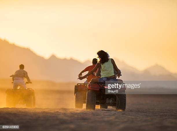 Rear view of friends on quad bikes in the desert.